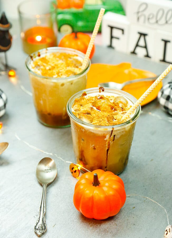 Pumpkin pie cold brew in glass cups filled with ice surrounded by Halloween decorations