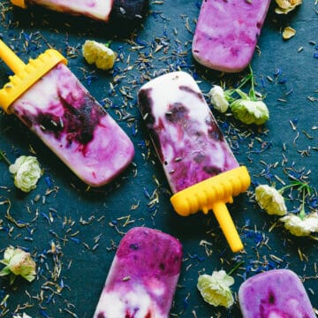 lavender blueberry coconut dairy free honey popsicles sitting on a black cutting board