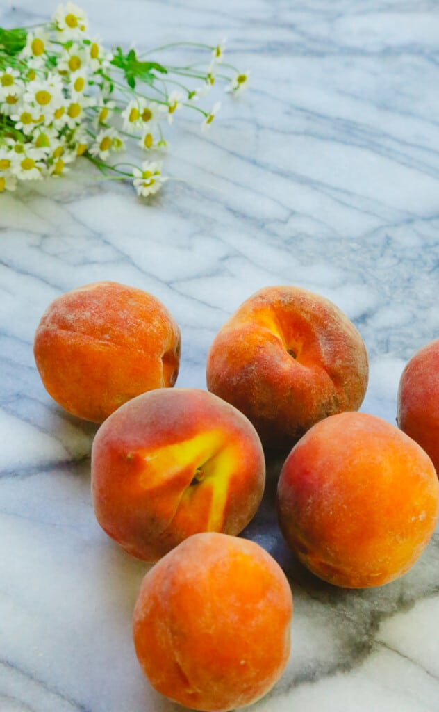peaches on a marble backdrop with chamomile flowers