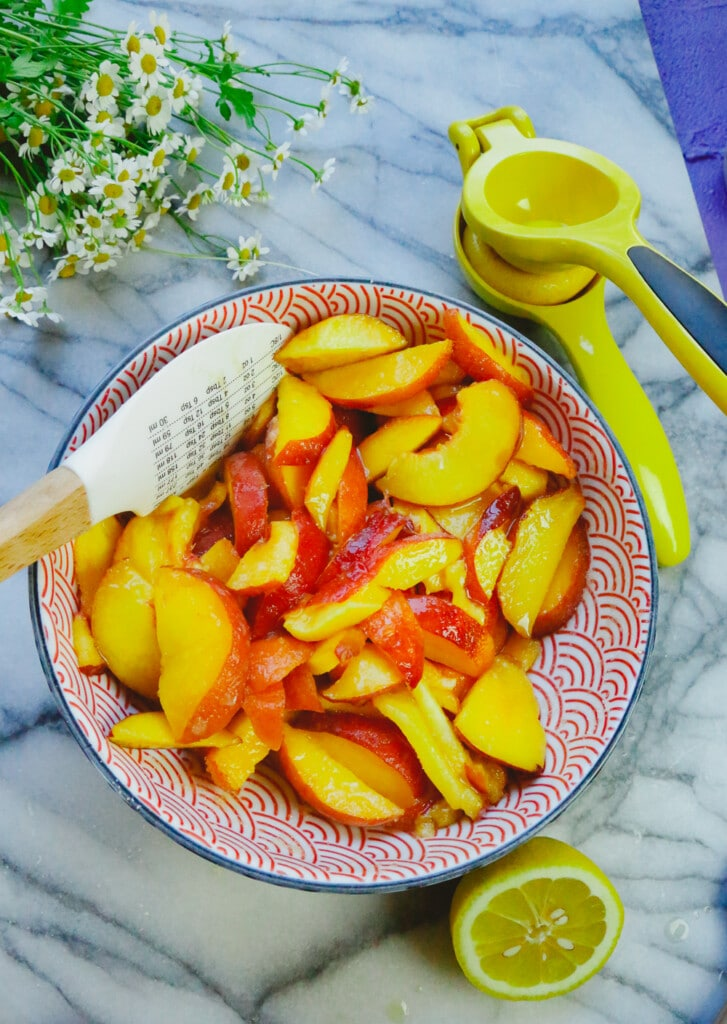 bowl of fresh sliced peaches with a lemon juicer and a mixing spoon