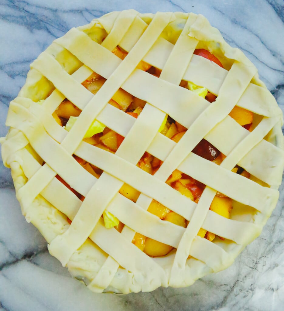 lattice pie crust topping with fresh peaches in a glass pie dish on a marble slab