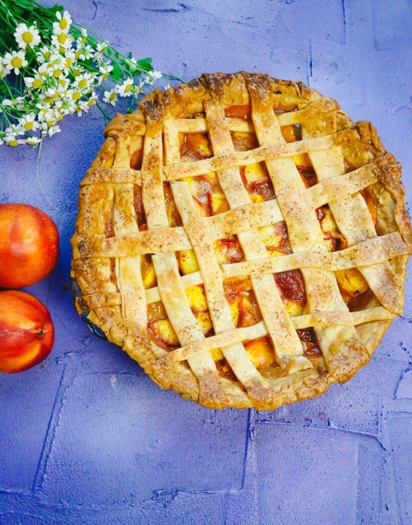 Golden brown pie made with a lattice crust and homemade peaches