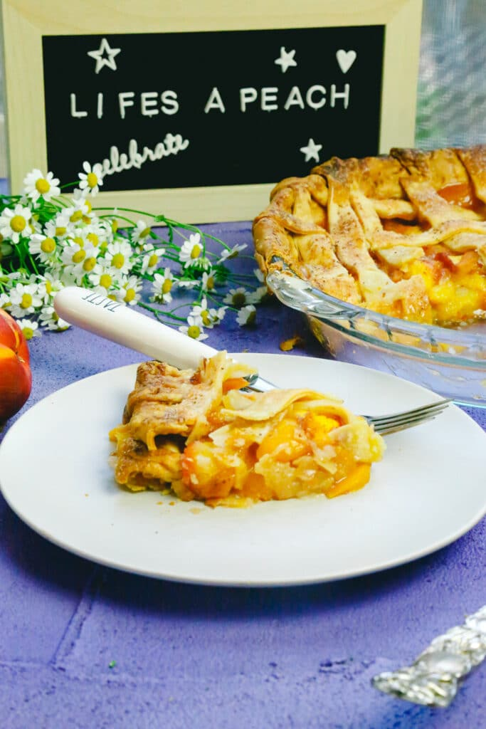 Homemade Honey peach pie on a plate with a fork and sign behind it made with lattice crust and fresh peaches