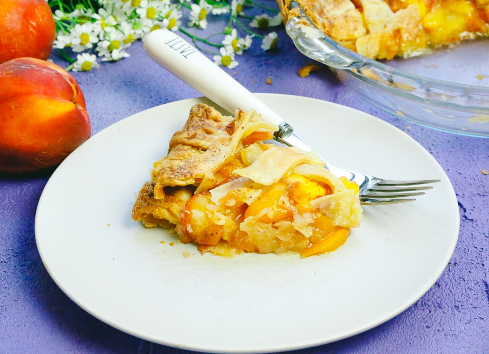 Slice of pie made with fresh peaches and honey served on a plate with a fork next to chamomile flowers