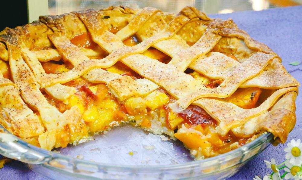 Honey peach pie with a lattice crust and fresh peach in glass pie plate