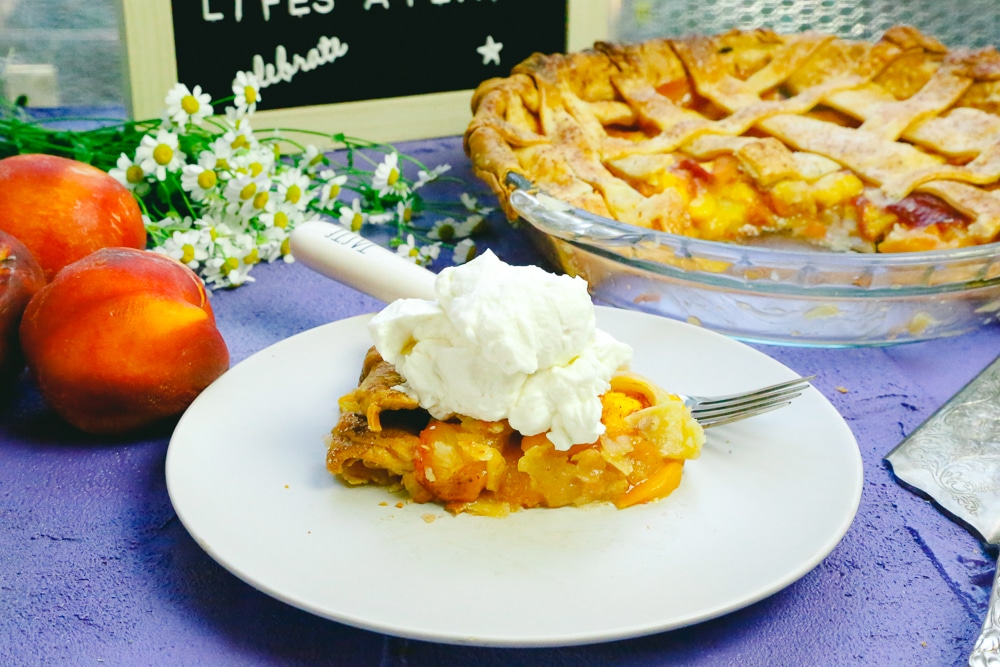 Slice of fresh peach honey pie with a dollop of fresh whip cream served on plate with a fork