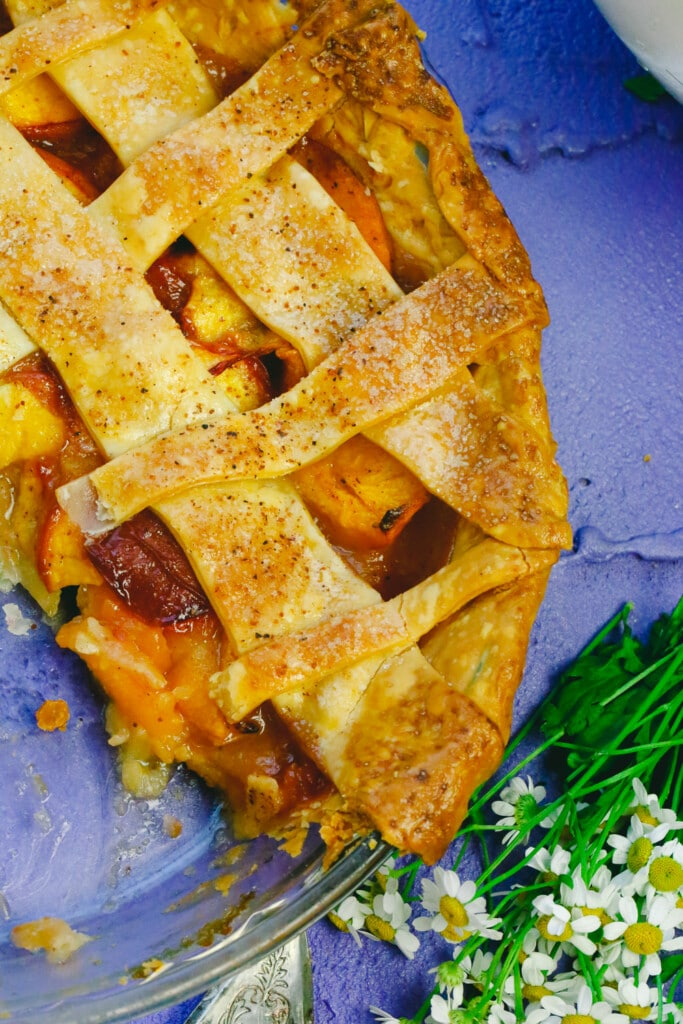 Whole peach pie with a golden brown lattice crust served in a glass pie dish