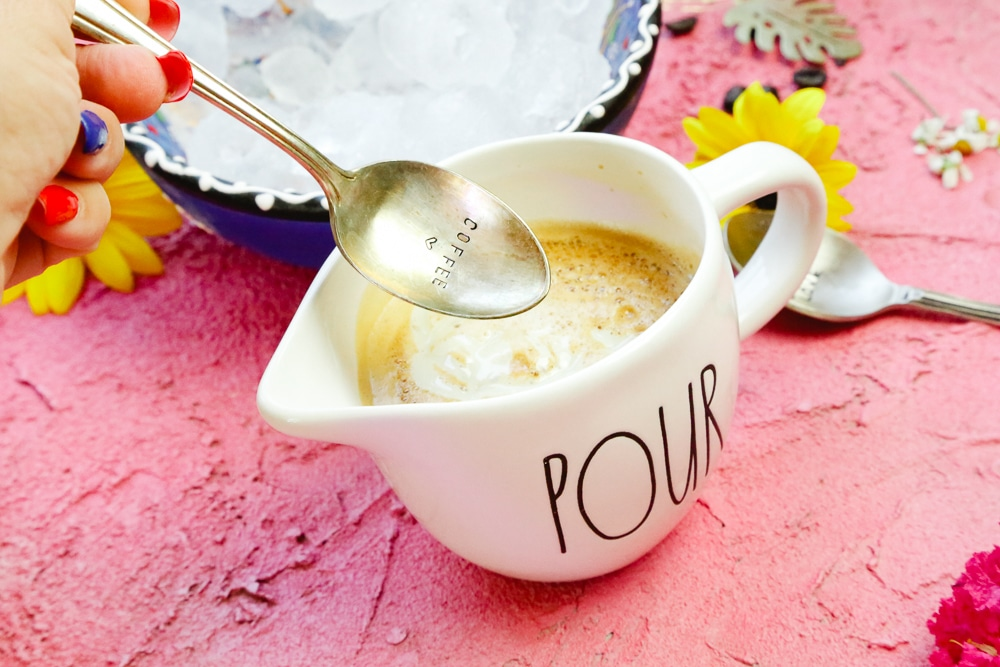 espresso made with sweet milk and coconut syrup stirred with a coffee spoon