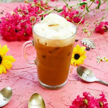 Iced coffee shakerato italian iced coffee with coffee spoon next to sunflower