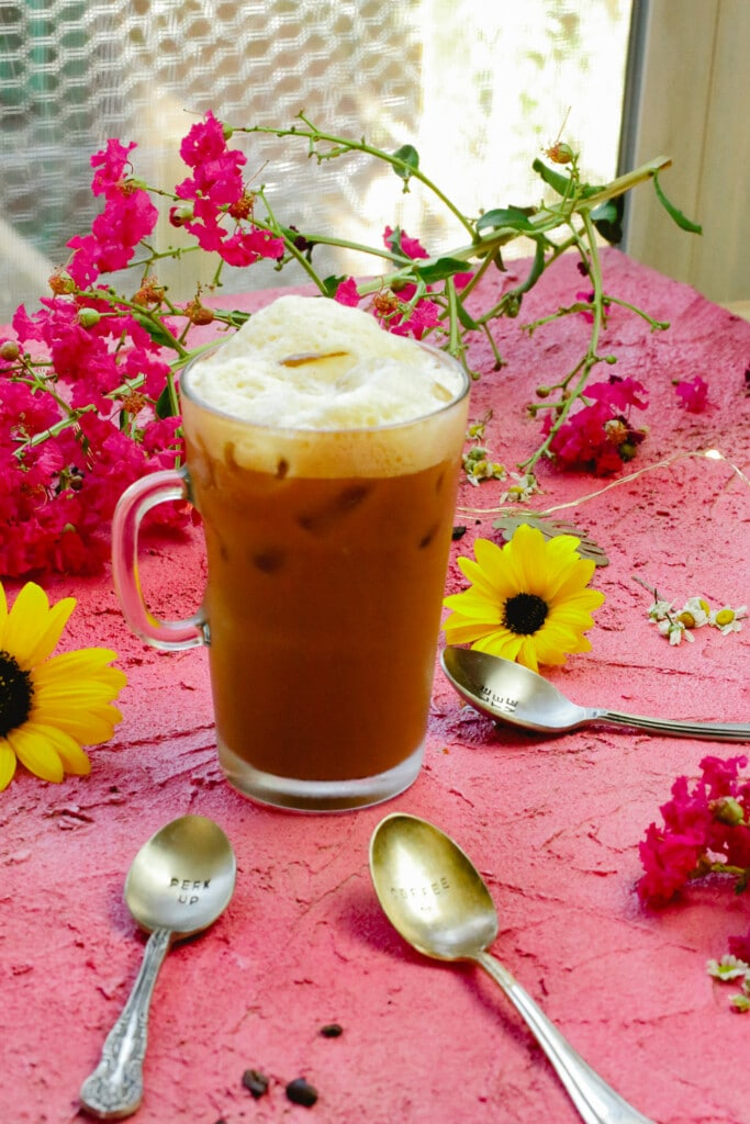 Foam topped iced coffee made with sweetened condensed milk, coconut syrup shakerato iced coffee with metal spoons