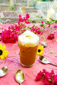Glass filled with foam and iced coffee shakerato with Italian espresso and sweet milk next to sunflowers