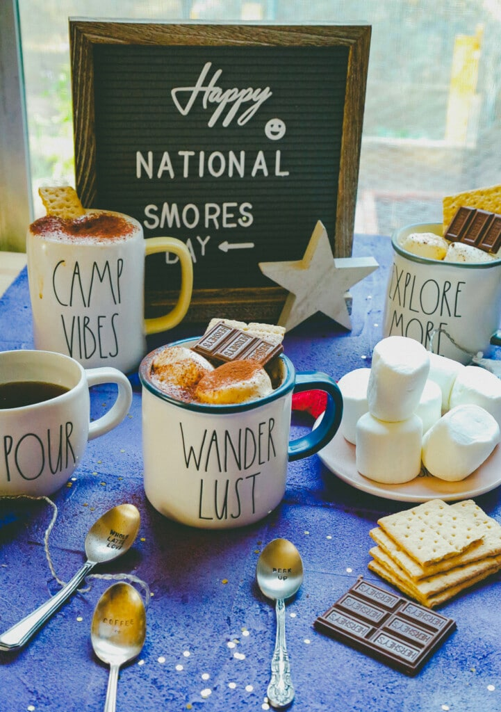three coffee mugs filled with  coffee and garnished with marshmallows and chocolate