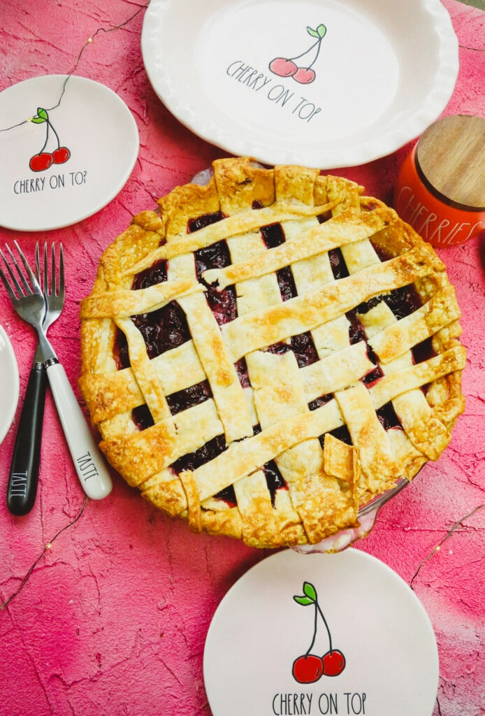 a lattice pie crust with cherries, forks, and cherry pie plates