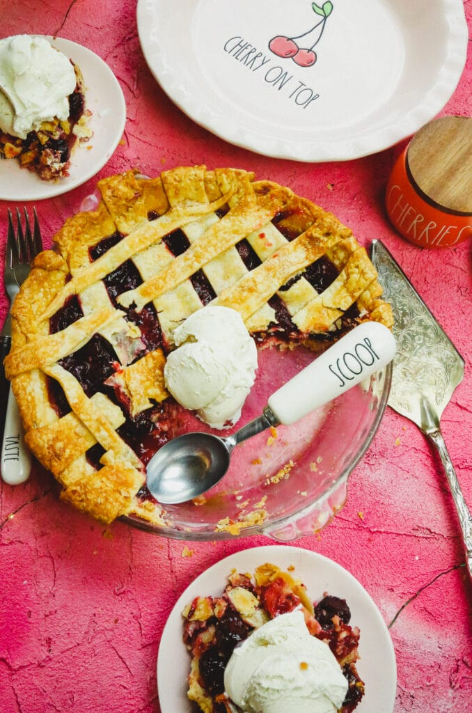 a pie plate with a cherry pie with a scoop of vanilla ice cream