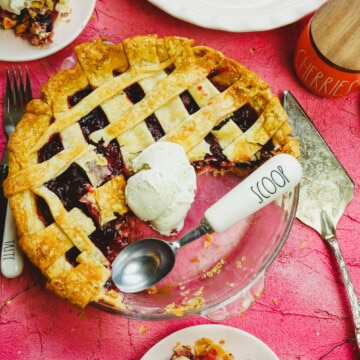 a pie plate with refined sugar free cherry pie and ice cream scoop and ice cream